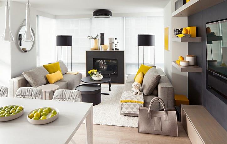 wohnzimmer modern mit akzentwand und kamin in schwarz, grauen sofas mit geben kissen und esstisch weiß
