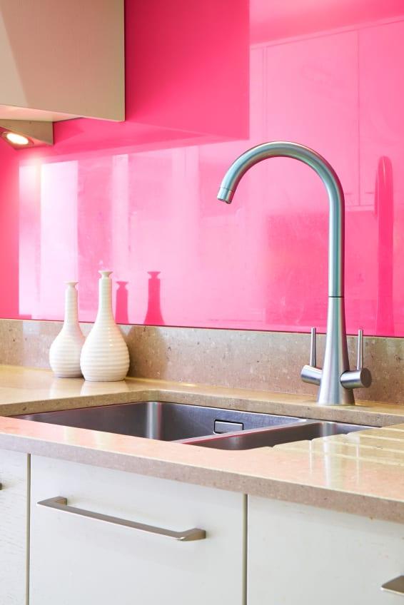 moderne küche einrichten mit küchenfront in pink, weißen kücjenschränken und küchenarbeitsplatte aus granit in beige