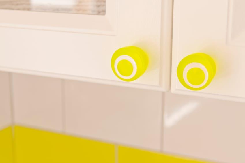 moderne küche einrichten mit weißen küchenschränken und gelben schrankgriffen