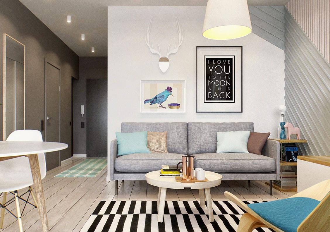 kleines wohnzimmer einrichten mit rundem couchtisch weiß vor sofa grau, pendellampe weiß, teppich mit schwarzweißen streifen und Wandfarbe grau