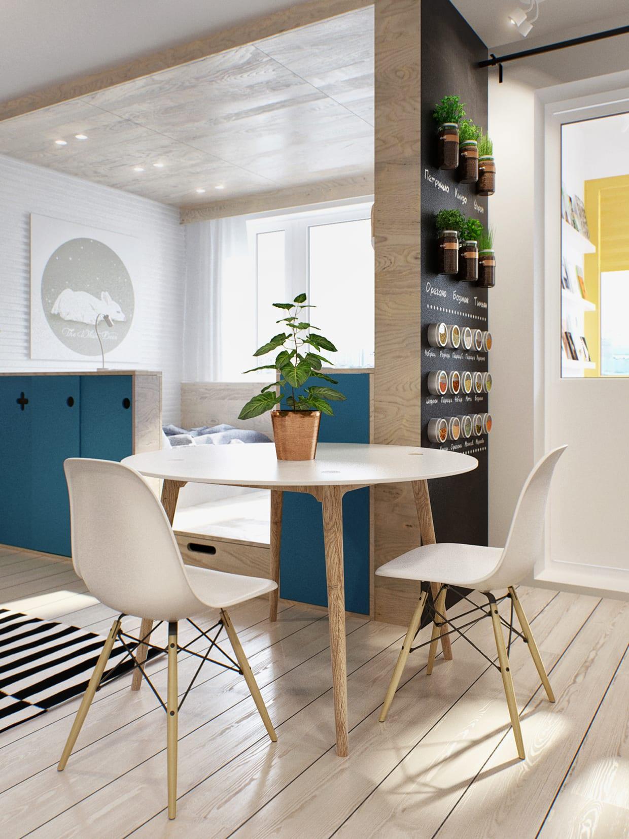 einraumwohnung mit akzentwand schwarz, weißem esstisch rund und weißen esszimmerstühlen