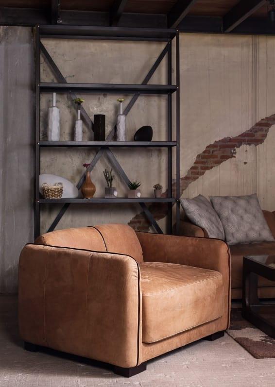 kreatives wohnzimmer design im Industrial Style mit Ledersessel in Cognac Farbe, Metallregal und coole Wandgestaltung