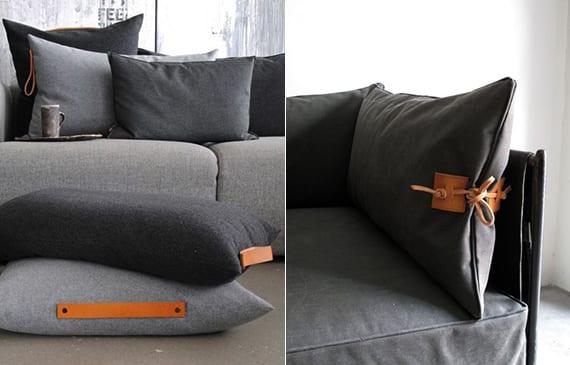 modernes innendesign in grau für moderne wohnzimmer mit grauem sofa und kissen mit ledergriffen