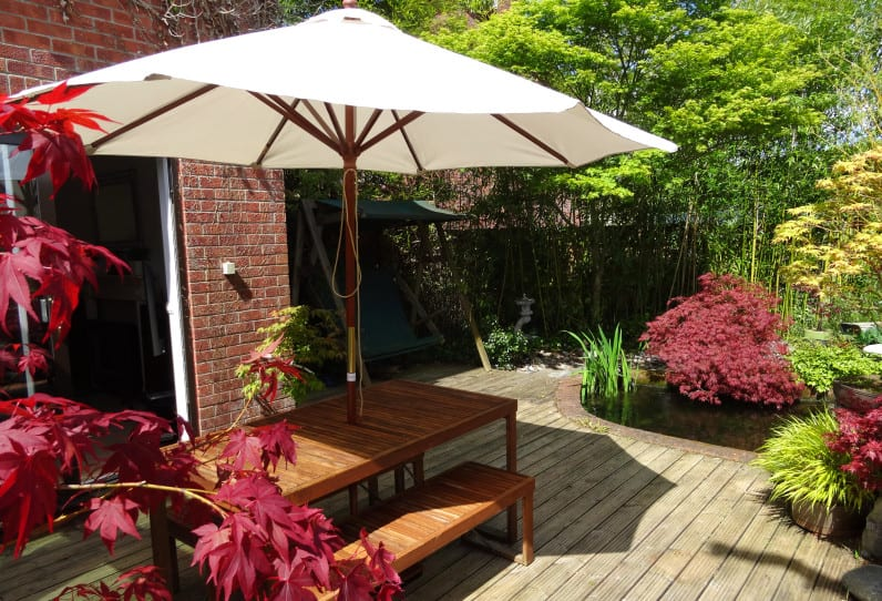 ein schönes wohnzimmer draußen auf holzterrasse mit teich einrichten mit sonnenschirm und holzgartenmöbeln