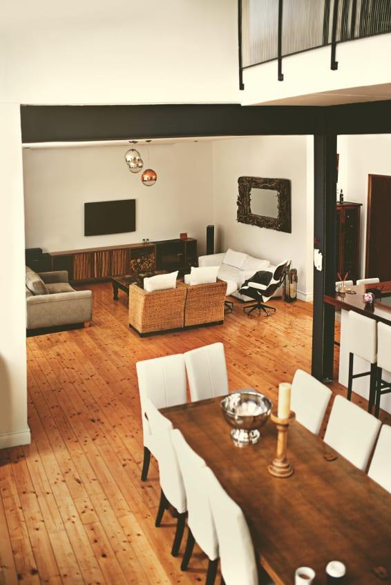 modernes wohn-esszimmer mit sichtbaren stahlträger schwarz und esstisch aus massivholz mit weißen esstischstühlen