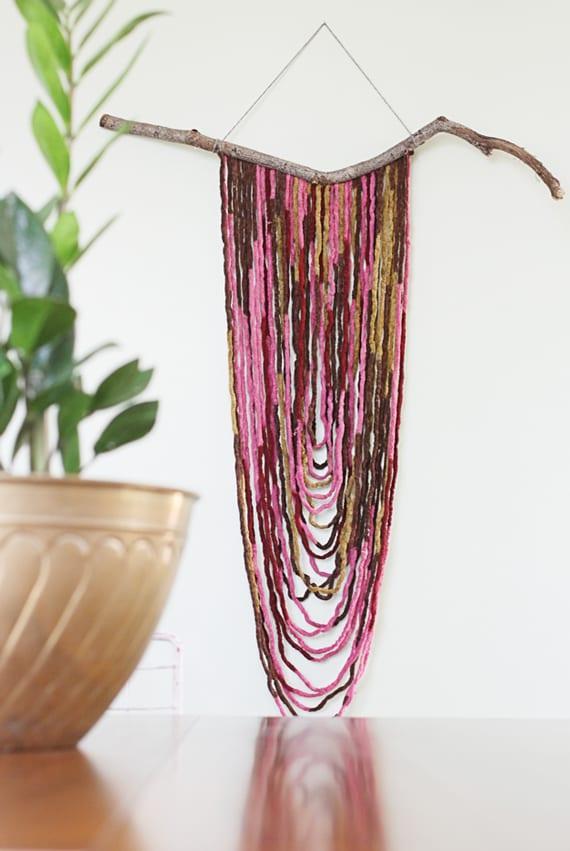 originelle wandgestaltung mit diy Wandbehang aus zweig und rosafarbigen garnfäden