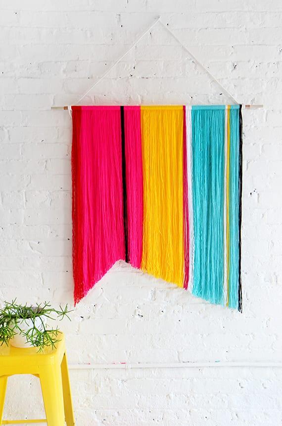 weiße wand dekorieren mit diy wandbehang in pink, gelb und blau_moderne wandgestaltung für weiße ziegelwand
