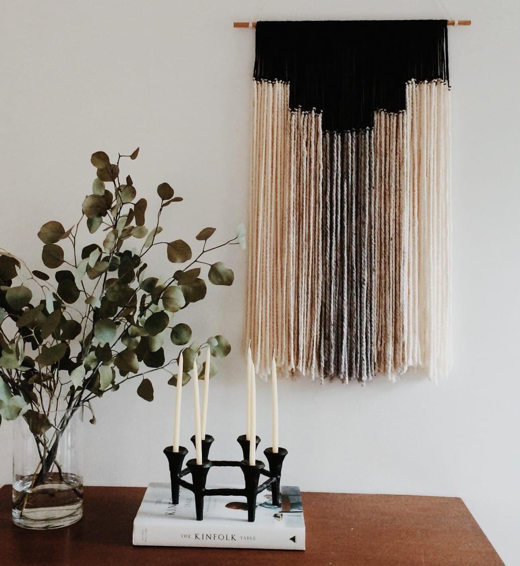 sideboard dekorieren mit schwarzem kerzenhalter und glasvase mit zweigen