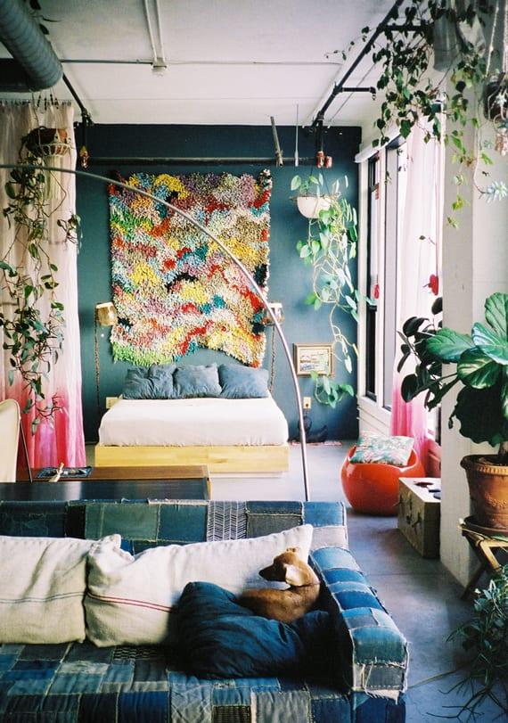 zimmer gestalten mit sofa pachwork in blau und akzentwand in blau mit wandbehang als wanddeko hinter holzbett