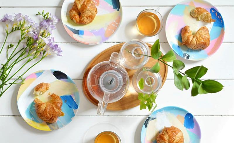 der feine tisch zum frühstück mit selbstgemachtem geschirr set und ovalem holtzschneidebrett