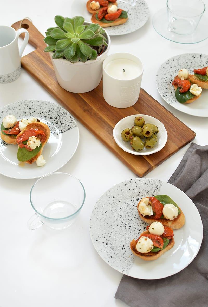 frühstückstisch kreativ decken mit geschirr sett in weiß und schwarz, kaffeegläser und holzschneidebrett mit kerzenhalter und blumentopf weiß