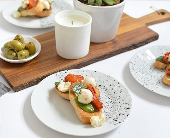 der gedeckte tisch zum frühstück mit selbstgemachtem geschirr weiss und holzschneidebrett mit kerze und fettpflanze als tischdeko