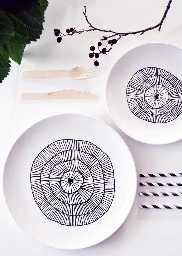 der feine tisch mit selbstgemachtem designer geschirr set aus weißen tellern mit schwarzen kreisen und strichen