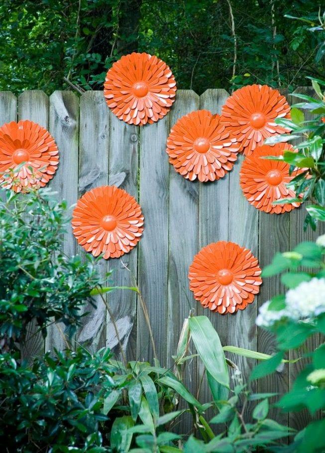 gartenmauer aus holz kreativ dekorieren mit orangen papier-blumen