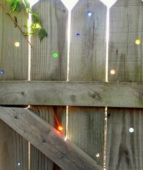 coole gartengestaltung und gartenmauer dekoidee mit farbigen glaskugeln