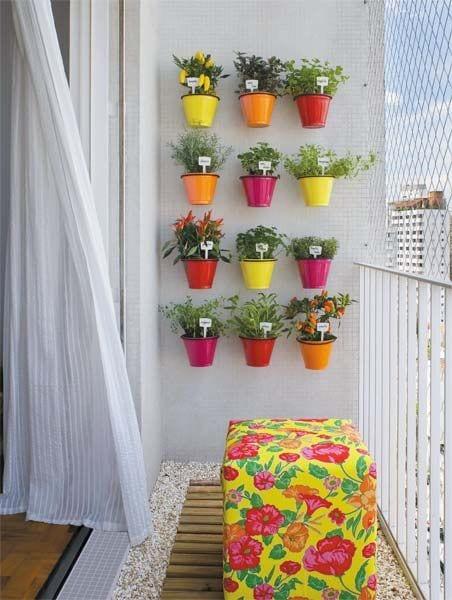 kleiner balkon kreativ gestalten mit Polsterhocker auf Holzlatten und Kies und farbigen Wand-Blumentöpfen in pink, gelb, rot und orange