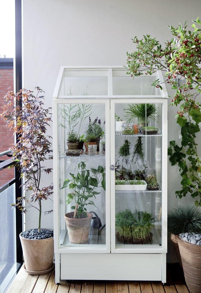 kreatives balkon design mit weißem vitrinenschrank als originelle balkonbepflanzung idee