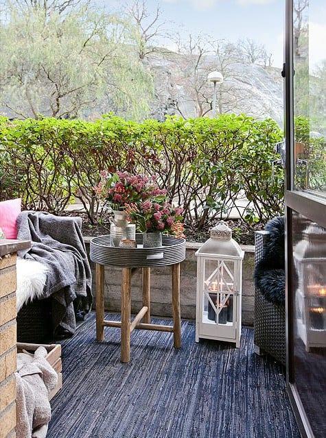 schöner balkon einrichten mit rattan-sesseln, schwarz-grauem Teppich, runder baistelltisch mit metallvasen und weißer garten-laterne