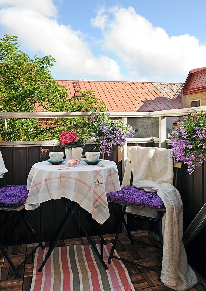 kleiner balkon mit holzgeländer romantisch einrichten mit rundem Klapptisch und zwei klappstühlen mit lilafarbigen sitzkissen