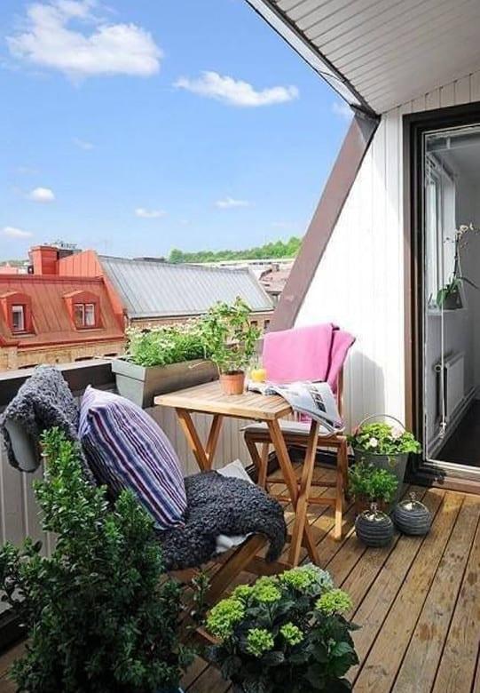frische balkon ideen für balkon einrichten als kleines wohnzimmer mit holzbodenbelag und gemütlicher sitzecke mit holzklapptisch und holzstühlen mit decken