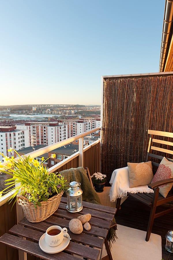 balkon gestalten mit holz-terrassenmöbeln, kissen in beige und strohzaun
