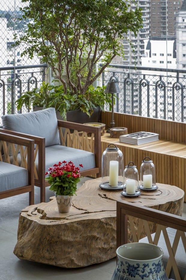 modernes balkon design mit holzbank, Baumstumpf-couchtisch, terrassenmöbel aus holz mit grauen polsterkissen und raumhoher Verglasung