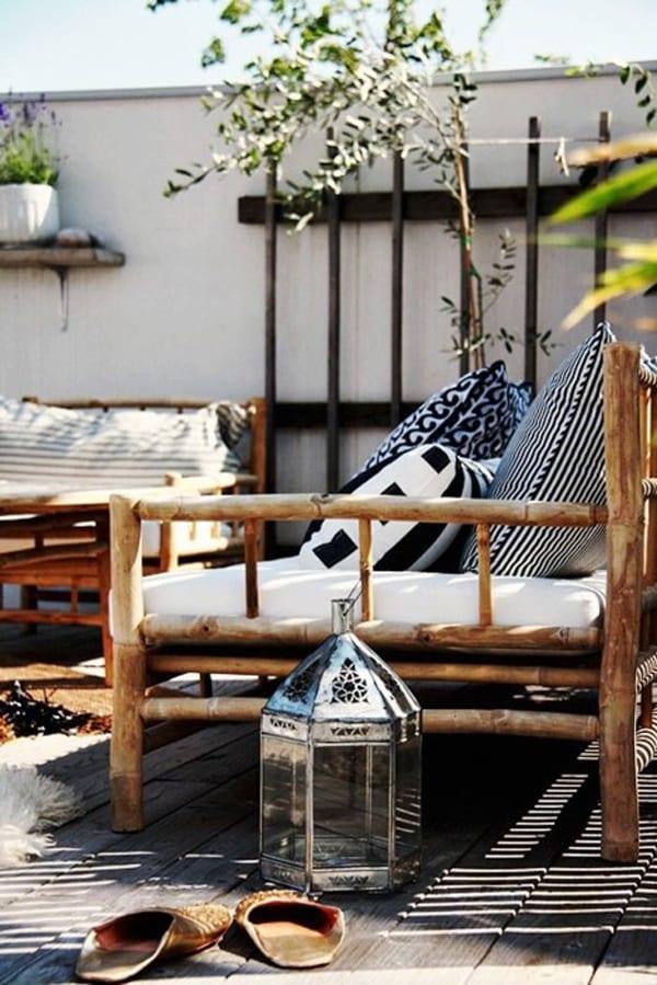 balkon design ideen in schwarzweiß mit gartenmöbeln aus bambus, orientalischer laterne und weißen dekokissen mit schwarzem muster