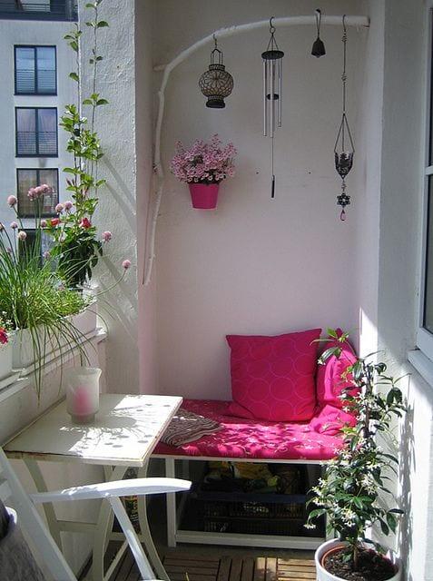 kleiner balkon ideen für balkon verschönern mit rosafarbiben kissen und blumentopf_coole ideen für kleine balkone in weiß und pink mit kleinem holztisch und sitzecke in weiß