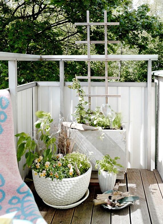 kleiner Balkon mit metallgeländer und textil-sichtschutz weiß dekorieren mit rundem Blumentopf weiß und DIY Hochbeet aus beton