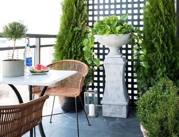 schöner balkon einrichten mit schwarzen bodenfliesen und schwarzer Holzgitter als sichtschutz