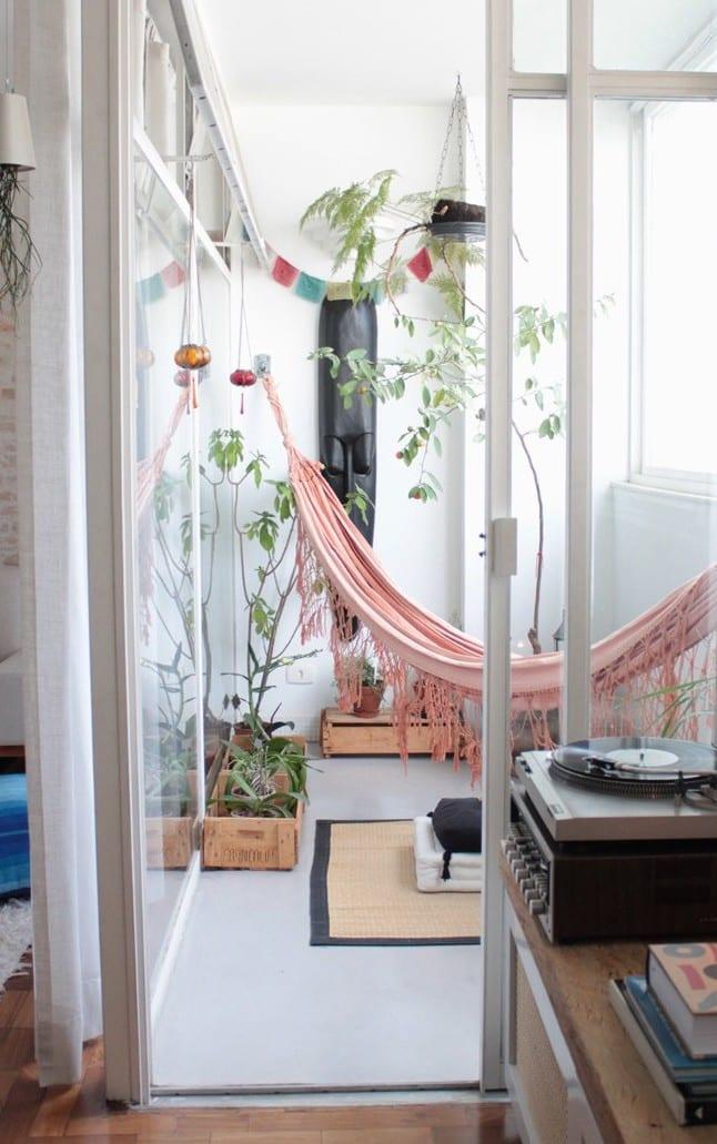verglaster balkon mit rosafarbiger hängematte und holzkisten als übertopf für pflanzen
