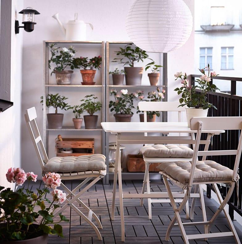 balkon design in weiß mit rechteckigem klapptisch, holzfliesen und zwei Metallregalen