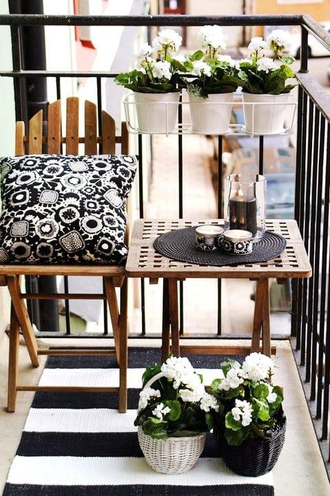 kleiner balkon mit schwarzem stahlgeländer modern einrichten mit teppichläufer, klapptuhl und klapptisch aus holz, weiße blumentöpfen und schwarzweißen dekokissen und weidenkörben