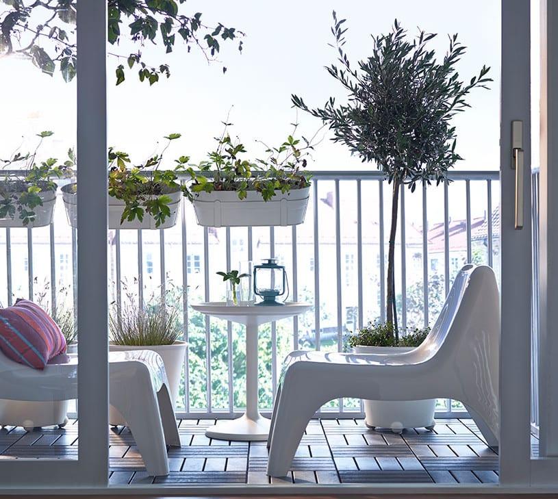 kleiner balkon modern einrichten in weiß mit holzfliesen und weißen blumentöpfen auf rollen