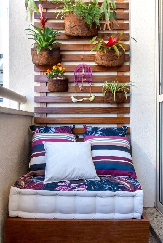 coole balkongestaltung für den kleinen balkon mit holzlatten und polster mit kissen in weiß, blau und pink für kleine sitzecke auf boden