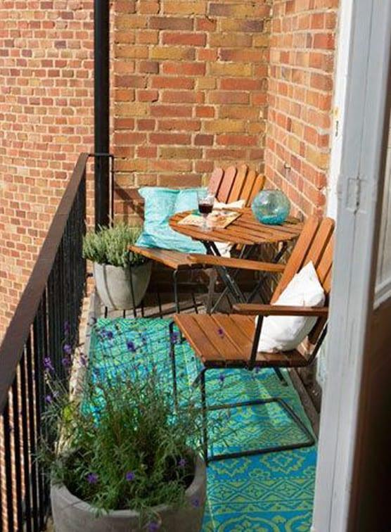 balkon mit stahlgeländer und holzboden kreativ gestalten mit rundem holztisch und holzstühlen auf blauem teppich und dekorieren mit zwei runden beton-blumentöpfen
