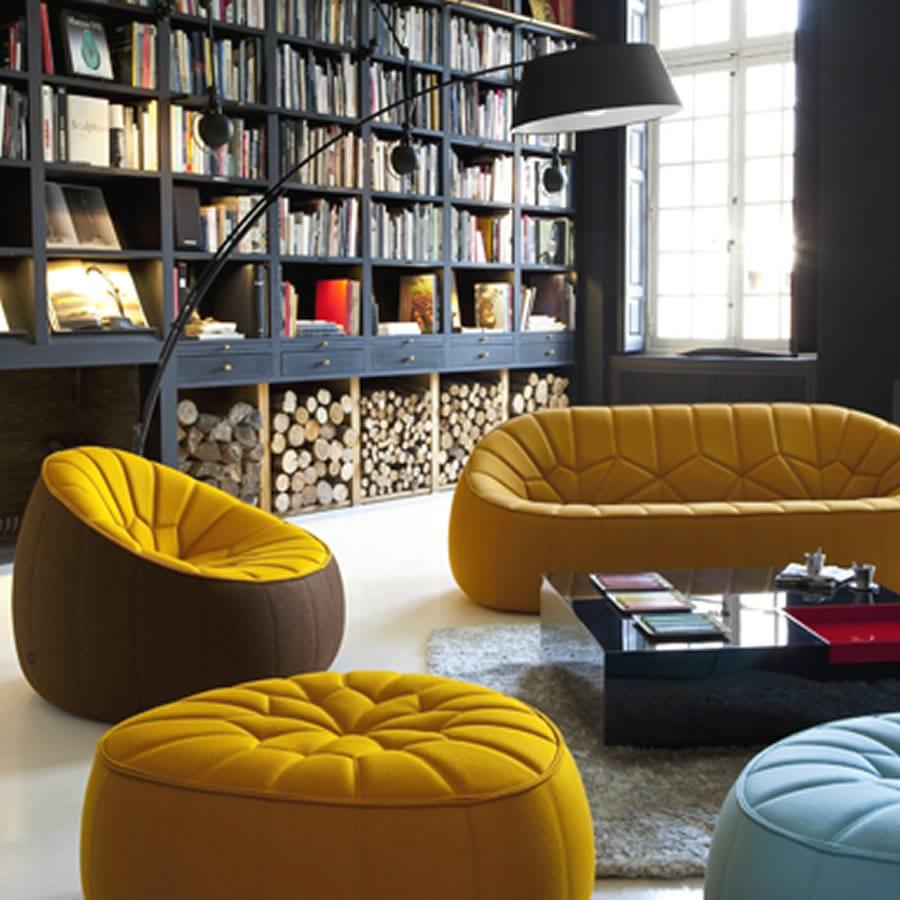 modern seats and sofas in gelb mit rechteckigem couchtisch in schwazlack und schwarte Stehlampe vor schwarzen wandbüchherregalen