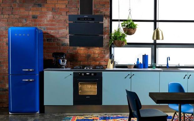 die küche mit blauen küchenschränken, ziegelwand und retro kühlschrank smeg als idee für moderne küchenausstattung in blau