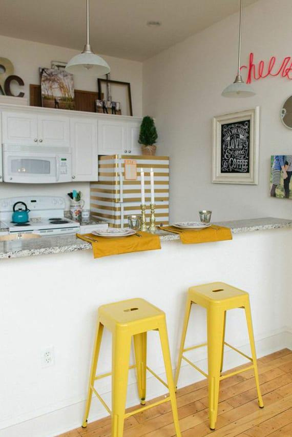 kleine weiße küche mit bar-theke, gelben barhocker,weißen holz-küchenschränken und diy retro kühlschrank mit streifenmuster in golz und weiß