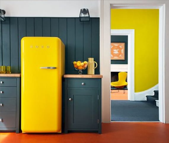 die küche in retrostil mit gelebem retro kühlschrank smeg und grauen küchenschränken und holzwandverkleidung