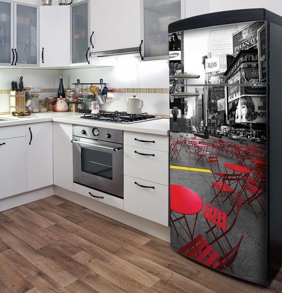 küchenausstattung mit weißen küchenschränken, parkett und schwarzem retro kühlschrank mit aufkleber
