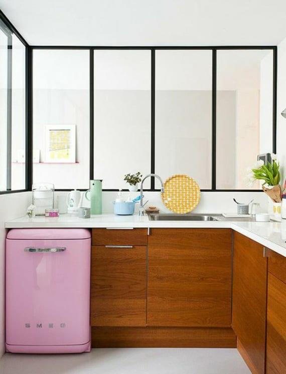 kleine eck-küche im wohnzimmer mit verglasung, eckarbeitsplatte weiß über holzküchenschrönken und kleinem retro kühlschrank in pink