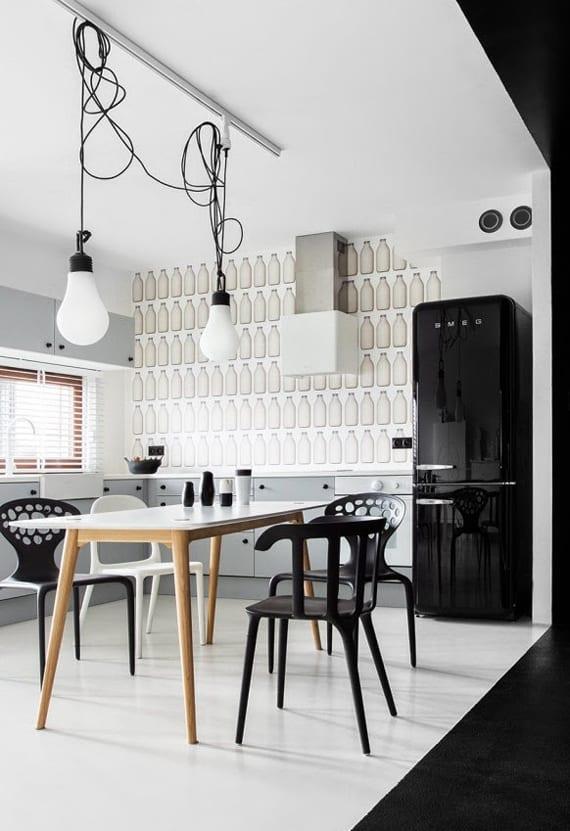 die küche in schwarz weiß mit retro kühlschrank schwarz, tapete mit milchflaschen, hellgrauen küchenschränken, und esstisch holz mit schwarzen esstischstühlen_coole wandgestaltung küche mit tapete und wandfarbe schwarz