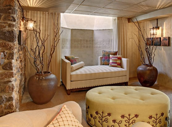 das kleine und moderne wohnzimmer im keller mit steinwand, großen vasen und ottomanen in beige