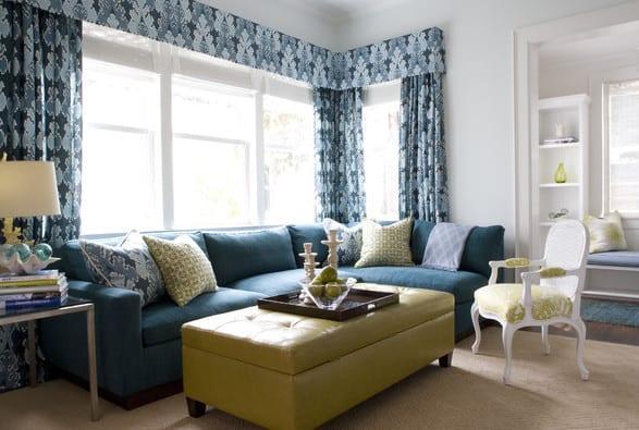 kleines wohnzimmer interior mit blauem ecksofa, gelbe ottomane aus leder und blauen gardienen
