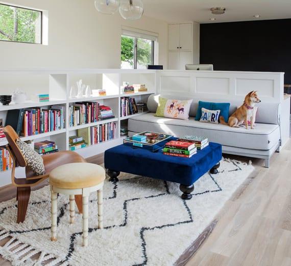 modernes wohnzimmer gestalten mit schwarzer wand, regal-raumteiler weiß und blauer ottomane_trennung vom arbeitzplatz im wohnzimmer