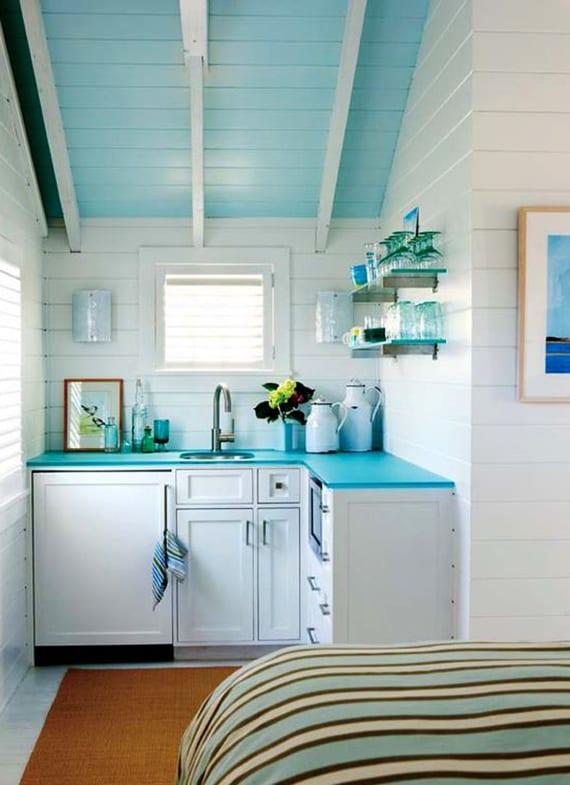 kleine weiße küche mit blauer küchenarbeitsplatte und blau gestrichene gachschräge mit holzverkleidung als coole farbgestaltung küche