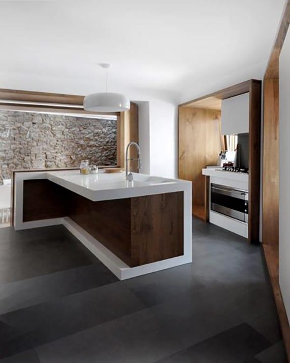 wohnküche mit schwarzen bodenfliesen und moderner Kochinsel aus Holz_kleine küche mit blick aufs esszimmer mit natursteinwand über öffnung mit holzrahmen