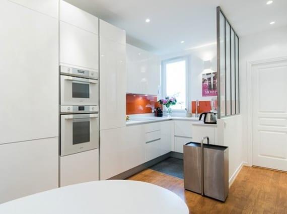 die weiße wohnküche modern gestalten mit küchenrückwand in orange, ovalem Esstisch, einbaugeräte und verglasung als raumteiler