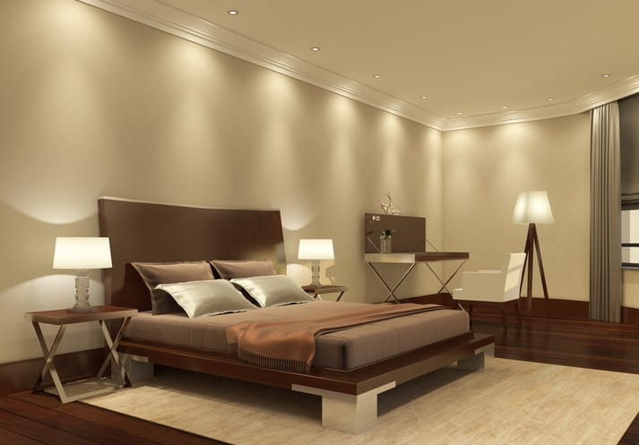 gemütliches schlafzimmer gestalten mit wandfarbe beige, dunklem holzfußboden, modernem holzbett mit bettkopfteil auf teppich in beige und deckenstrahler kombiniert mit nachttischlampen auf designer nachttisch aus metall